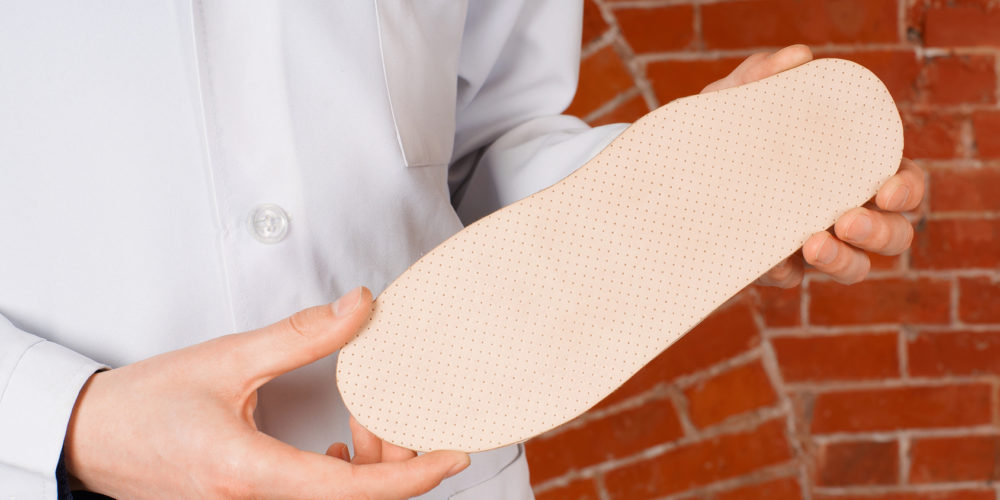 Doctor shows orthopedic insoles